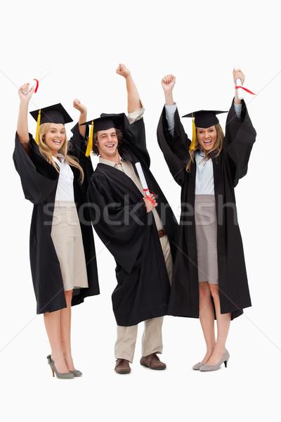 Tre studenti laurea robe braccia bianco Foto d'archivio © wavebreak_media
