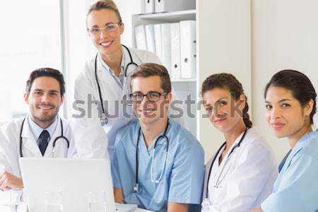 Medical team standing upright holding blank sheets in front of the bright window Stock photo © wavebreak_media