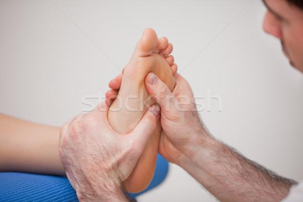 Podiatrist practicing reflexology on the foot of woman in a room Stock photo © wavebreak_media