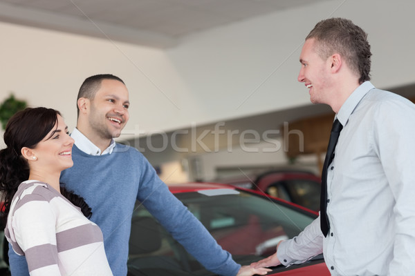 Risonho casal falante vendedor carro compras Foto stock © wavebreak_media