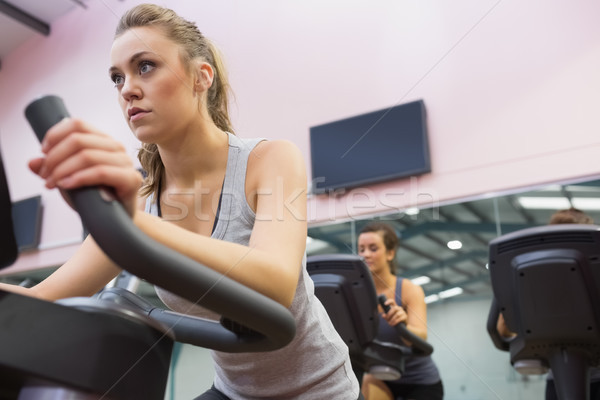 Woman training on exercise bike in a spinning class in gym Stock photo © wavebreak_media