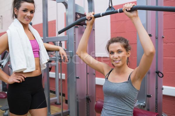 Friend stands beside woman using weights machine in gym Stock photo © wavebreak_media