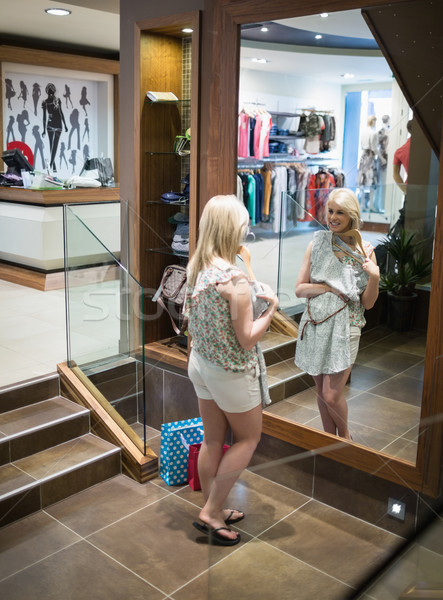 Woman is standing in front of the mirror at the boutique Stock photo © wavebreak_media