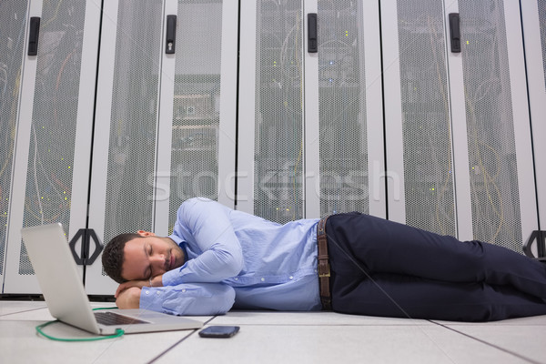 Man sleeping while doing maintenance on servers with laptop Stock photo © wavebreak_media