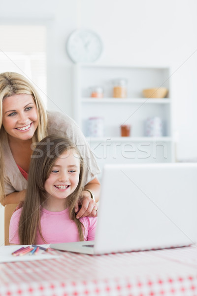 Stock photo: Laughing mother and girl looking at laptop in the kitchen