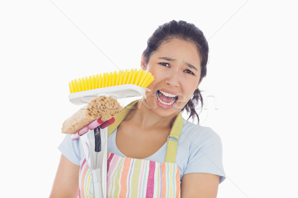 Frightened woman wearing apron holding mop and a broom Stock photo © wavebreak_media