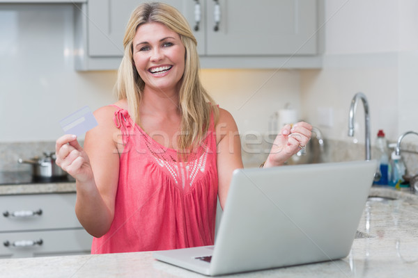 Excited woman with clenched fists using laptop in the kitchen Stock photo © wavebreak_media