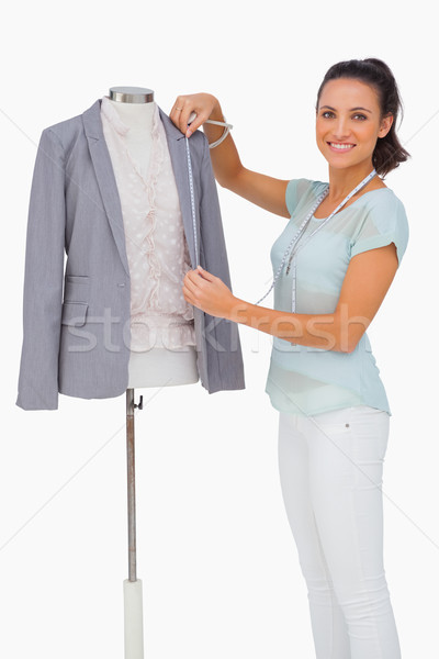 Fashion designer measuring blazer lapel on mannequin and smiling Stock photo © wavebreak_media