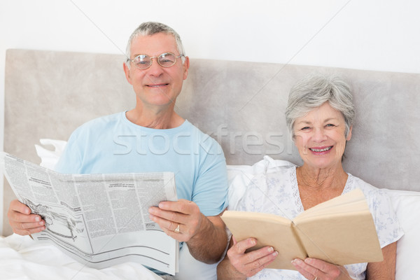 Stock photo: Senior couple holding newspaper and book in bed