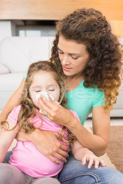 Caring mother helping her little daughter blow her nose Stock photo © wavebreak_media