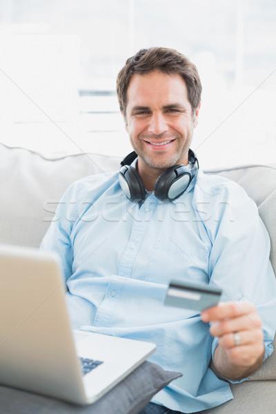 Smiling man sitting on sofa online shopping with laptop Stock photo © wavebreak_media