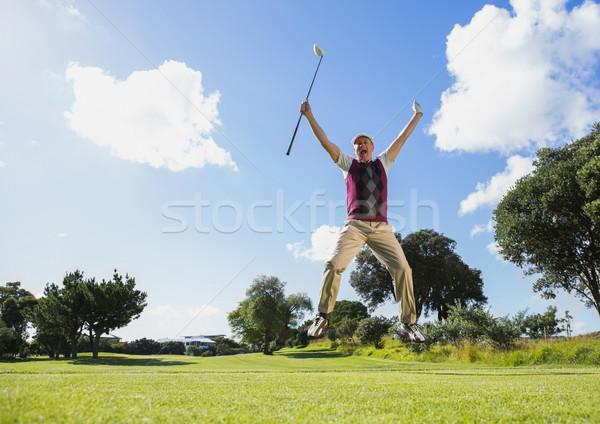 Excited golfer jumping up holding club Stock photo © wavebreak_media