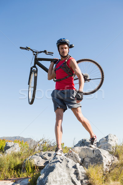 Fit cyclist carrying his bike on rocky terrain Stock photo © wavebreak_media