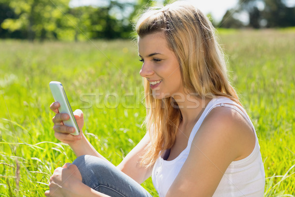 Pretty blonde sitting on grass sending a text Stock photo © wavebreak_media