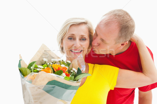 Mature man kissing his partner holding flowers Stock photo © wavebreak_media