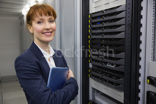 Pretty technician smiling at camera beside server holding tablet Stock photo © wavebreak_media