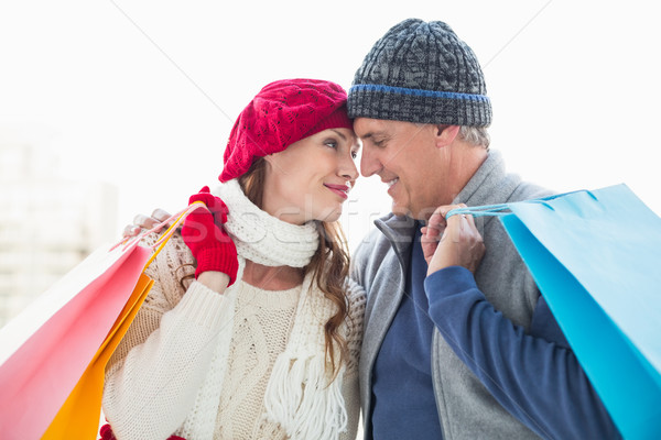 Happy couple in warm clothing with shopping bags Stock photo © wavebreak_media
