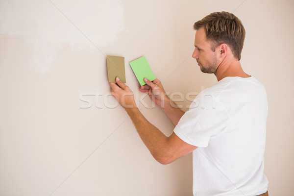 Handsome decorator sanding down the wall  Stock photo © wavebreak_media