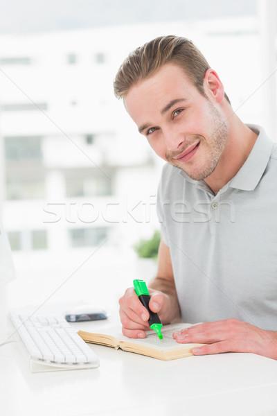 Cheerful casual businessman highlighting a book Stock photo © wavebreak_media