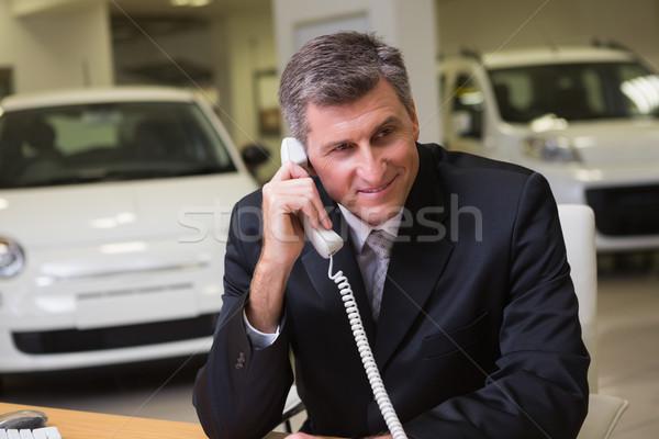 Sorridente empresário usando laptop telefone sala de exposição Foto stock © wavebreak_media