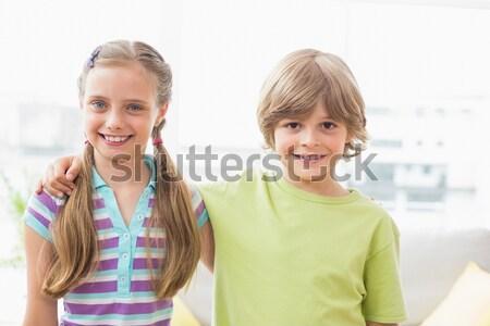Cute siblings standing arm around on white background Stock photo © wavebreak_media