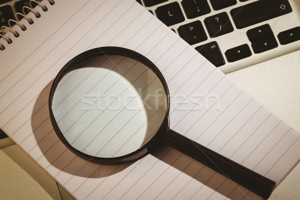 Magnifying glass and notepad on laptop Stock photo © wavebreak_media