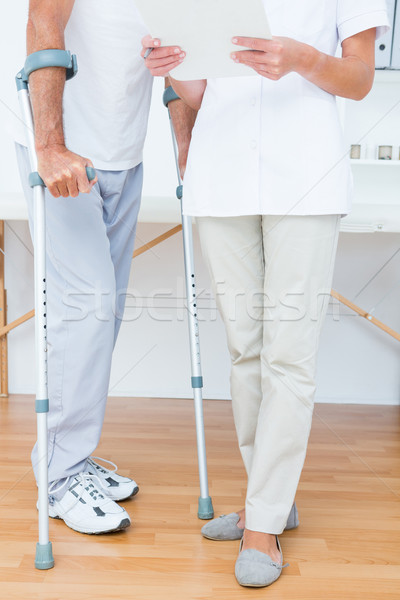 Doctor showing clipboard to her patient with crutch Stock photo © wavebreak_media
