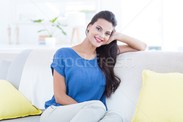 Smiling beautiful brunette relaxing on the couch and looking at  Stock photo © wavebreak_media