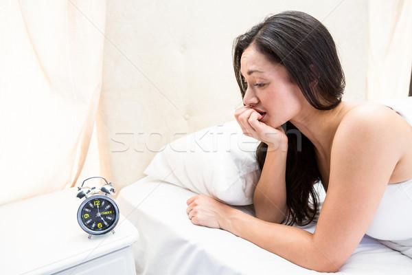 довольно брюнетка смотрят будильник кровать домой Сток-фото © wavebreak_media