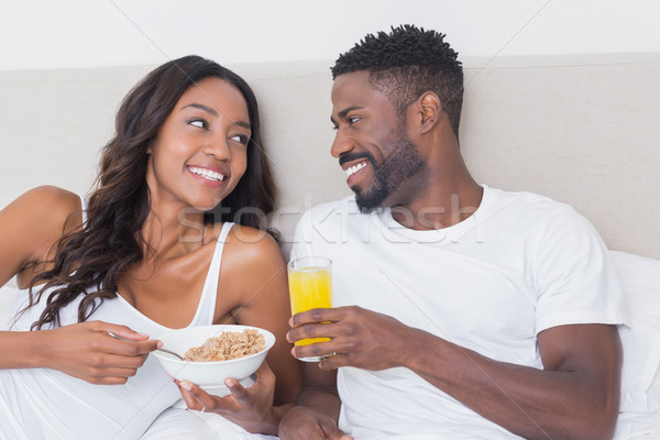 Relaxed couple in bed together eating cereal Stock photo © wavebreak_media