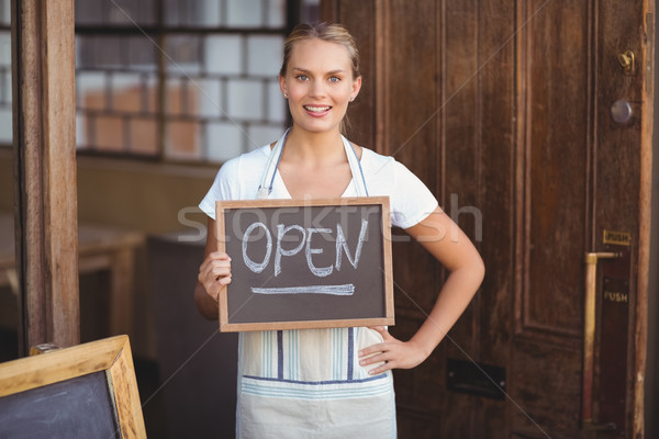 Smiling waitress showing chalkboard with open sign  Stock photo © wavebreak_media
