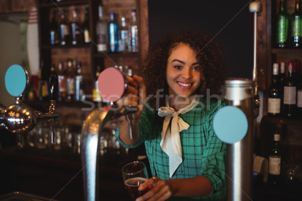 Portrait of waitress using beer tap at counter Stock photo © wavebreak_media