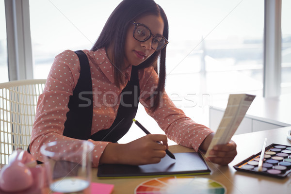 Focused businesswoman working on digitizer at office Stock photo © wavebreak_media