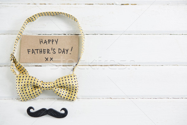 Happy fathers day text with bow tie and mustache on table Stock photo © wavebreak_media