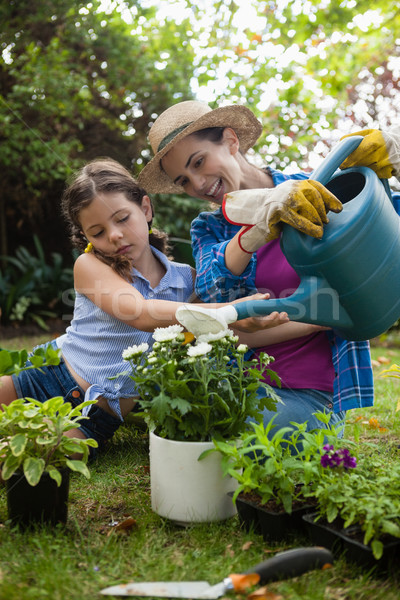 Happy mother with daughter watering potted plants in backyard Stock photo © wavebreak_media