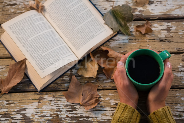 Cropped hand holding coffee cup by book on wooden table Stock photo © wavebreak_media