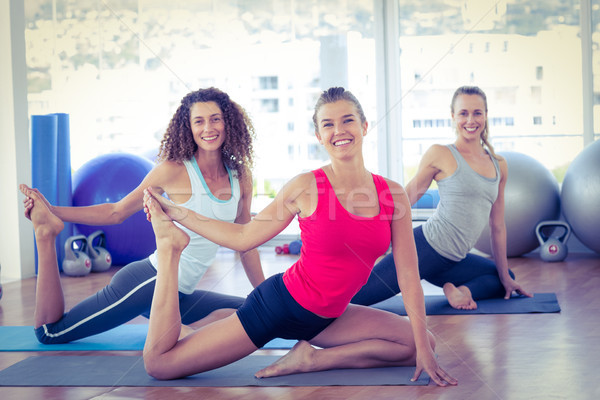 Women doing pigeon pose with one hand right leg grab Stock photo © wavebreak_media