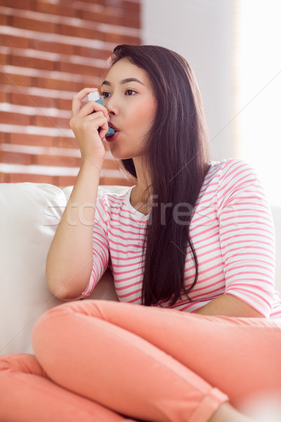Asian woman using her inhaler on couch Stock photo © wavebreak_media