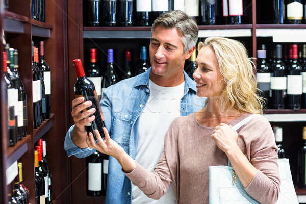 Smiling couple looking at bottle of wine  Stock photo © wavebreak_media