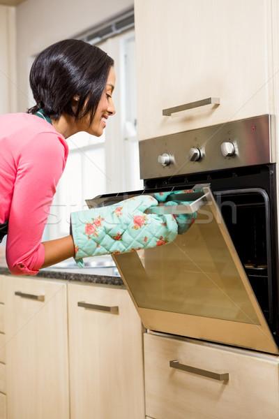Donna sorridente guardando forno home cucina femminile Foto d'archivio © wavebreak_media
