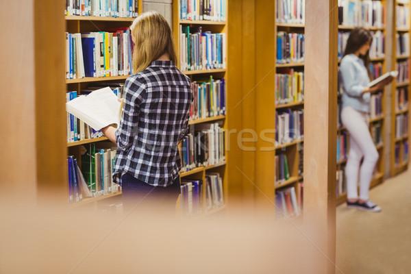 Ernstig studenten lezing boekenplank bibliotheek vrouw Stockfoto © wavebreak_media