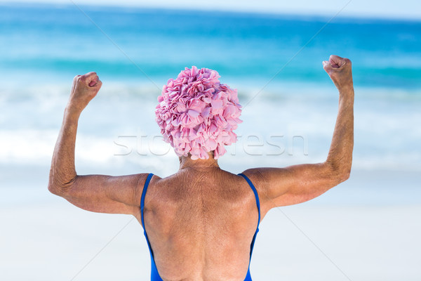 Pretty mature woman showing her muscles on the beach Stock photo © wavebreak_media