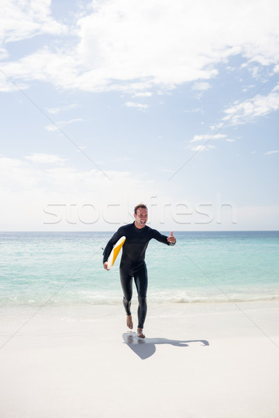 Surfista ejecutando playa tabla de surf hombre Foto stock © wavebreak_media