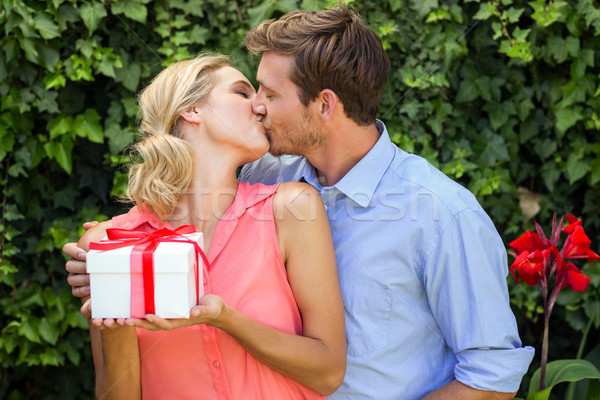 Man kissing while giving gift to woman at front yard Stock photo © wavebreak_media