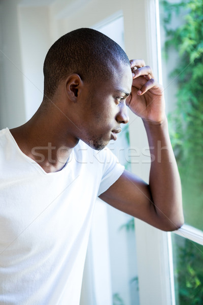 Thoughtful young man looking out of the window Stock photo © wavebreak_media
