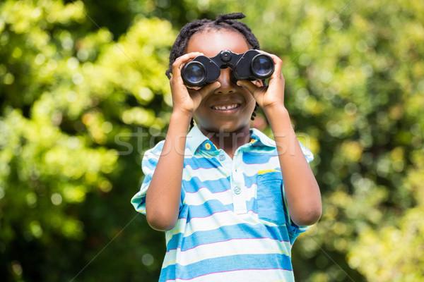 Smiling boy using magnifying glass Stock photo © wavebreak_media