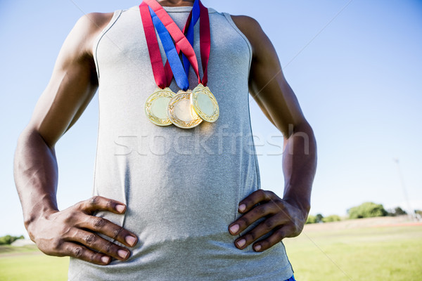 Athlete posing with gold medals around his neck Stock photo © wavebreak_media