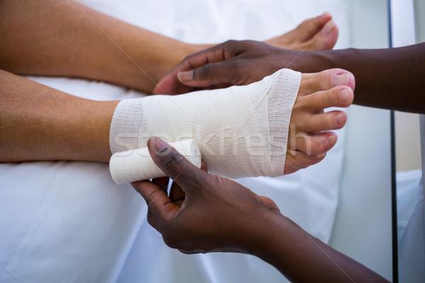 Doctor bandaging patients leg Stock photo © wavebreak_media