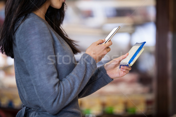 Woman holding dairy product and using mobile phone Stock photo © wavebreak_media