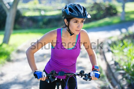Female cyclist cycling in countryside on sunny day Stock photo © wavebreak_media